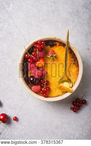 Creme Brulee With Raspberry  On Light  Baking Sheet. Space For Your Caption. Creme Brulee With Raspb