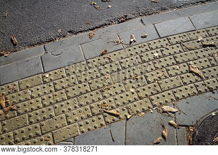 Textured Walkway For Blind People. Yellow Tactile Paving For The Visually Impaired On The Sidewalk.