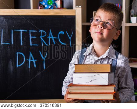 Portrait Of Cute Little Boy Holding Book In Classroom. Happy International Literacy Day. First Day O