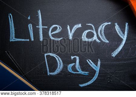 International Literacy Day Concept Pile Of Books On Blackboard. International Literacy Day