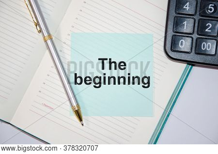 The Text The Beginning Is Written On A Paper Blue Block Near A Calculator And Notepad. Pen Next