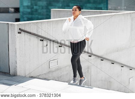 fitness, sport and healthy lifestyle concept - young african american woman running upstairs outdoors