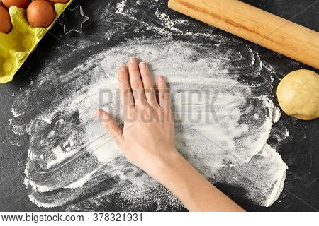 cooking food and culinary concept - hand with flour, dough, rolling pin and eggs on table