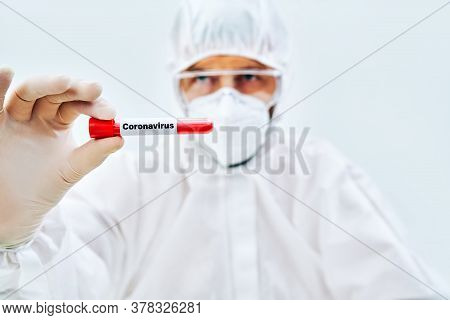 Doctor In Protective Suit Showing Coronavirus Infected Blood Sample Test Tube. Diagnosis, Infection
