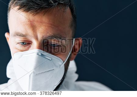 Exhausted Doctor In Ppe Suit Uniform In Stress On Black Background. Depression, Tired Concept. Close