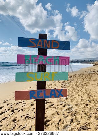 Wooden Signpost With Name Of Relax On Sand Beach Over Blurred Tropical Blue Sea On Day Noon Light.