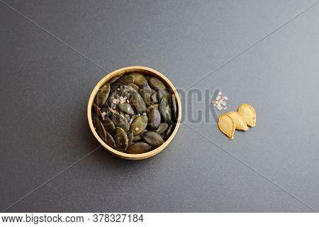 Peeled Pumpkin Seeds With Coarse Salt On A Gray Background.