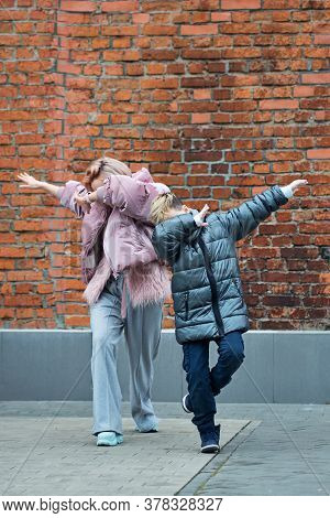 Trendy Hipster Family Making Dab Gesture, Having Fun On The City Street. Happy Mum And Son On Walk.