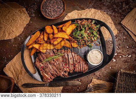 Gilled Beef Steak And Potatoes Served With Pepper Sauce And Lettuce On Black Plate, Top View