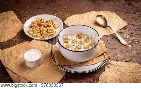 Delicious Garlic Cream Soup Served With Croutons In White Bowl