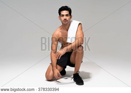 Young Latin Athletic Man With Towel On Shoulder Kneeling In Studio With Gray Background