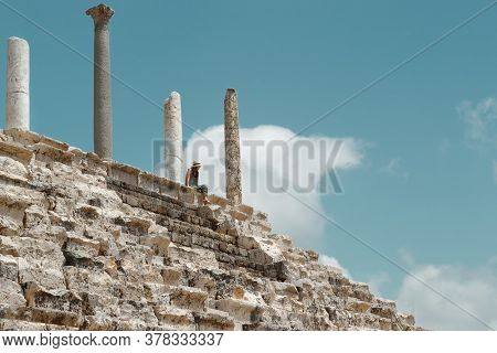 Tourist Woman Sitting on the Top of Ruins Of Tyre. Enjoying Beauty and Majesty of Necropolis. Travel to Lebanon. World Heritage.