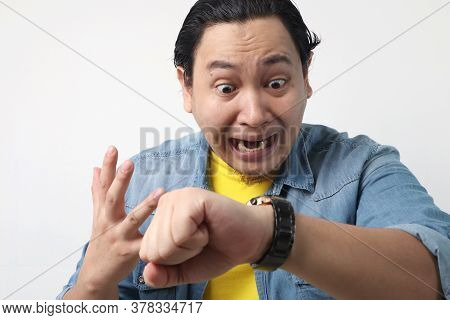 Young Asian Man Worried By Time When Looking At His Wristwatch. Work Or School Time Deadline
