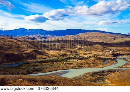 Shallow river with glacial melt water. South America. Patagonia. Dirt road among yellowing grass. The magnificent park of Torres del Paine. The concept of extreme tourism