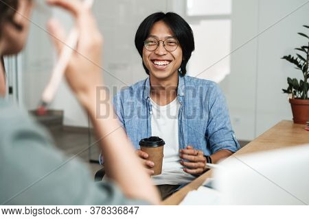 Image of multinational joyful colleagues discussing project and laughing while working in office