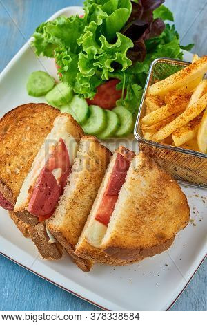 Grilled And Pressed Toast With Turkish Sausage, Cheese, Tomato And Lettuce Served On White Plate.