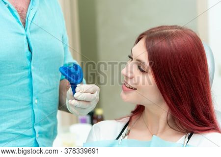 Doctor Orthodontist Shows The Patient The Result Of The Casts Of Her Teeth
