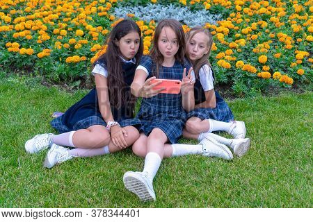 Three Teen Girls Take A Selfie Phone On A Sunny Day And Laugh. Emotions And New Technologies.