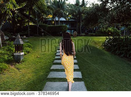 Young Woman Walks In A Yellow Dress On A Tropical Grove With Green Grass On A Sunny Day. Tropical Va