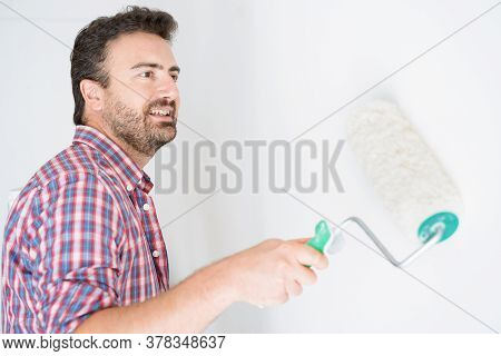 One Guy Whitewashing The Wall For Room Renovation