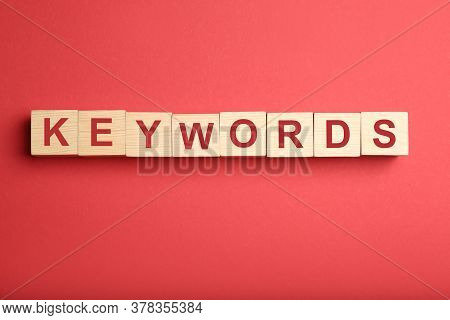Wooden Cubes With Word Keywords On Red Background, Flat Lay