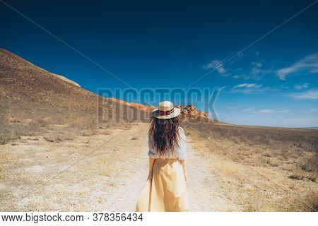 Beautiful Woman's Back In A Hat And Dress In The Mountains. The Girl Walks Along The Path To The Mou