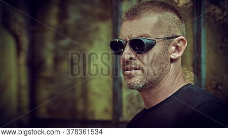 Portrait of a handsome brutal mature man with short hair and bristles wearing trendy sunglasses. Manly style. Optics for men.