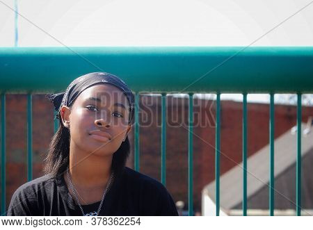 A Portrait Portrait Of A Beautiful African-american Teenaged Girl Standing Alone Outside And Feeling