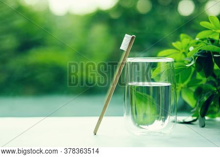 One Bamboo Toothbrushe In A Cup And Glass With Water