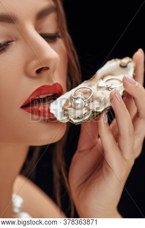 Close up of portrait of a gorgeous woman with pearls jewelry in an oyster shell. Jewelry concept.
