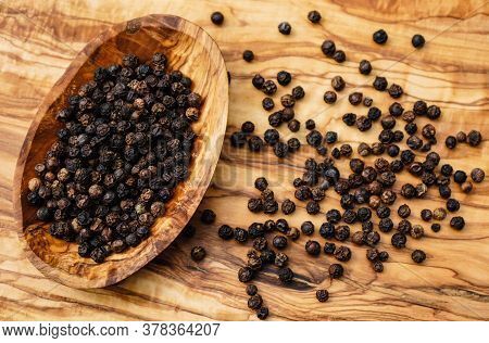 Many Black Peppercorns On A Wooden Table