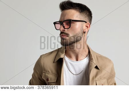 cool unshaved fashion guy in jacket wearing sunglasses and looking to side on grey background