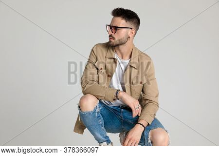sexy young casual model wearing beige jacket and sunglasses, looking to side, holding elbows on knees, bending the knee and crouching on grey background