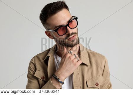thoughtful unshaved young man in jacket wearing sunglasses, touching chin and thinking, looking to side and posing on grey background
