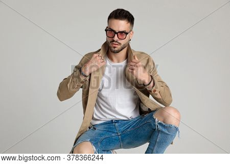young unshaved casual guy wearing sunglasses, looking to side and fixing jacket, holding elbows on knees and crouching on grey background