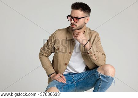 thoughtful unshaved young model wearing beige jacket and sunglasses, looking to side, holding hand to chin and thinking, holding elbows on knees and crouching on grey background
