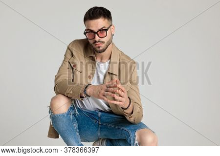 young casual guy in jacket wearing sunglasses, touching fingers, holding elbows on knees and crouching on grey background