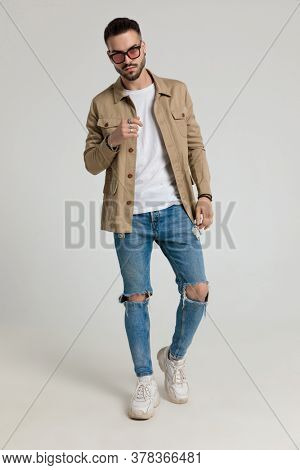 sexy young unshaved model in jacket wearing sunglasses holding hands in a fashion pose and walking on grey background