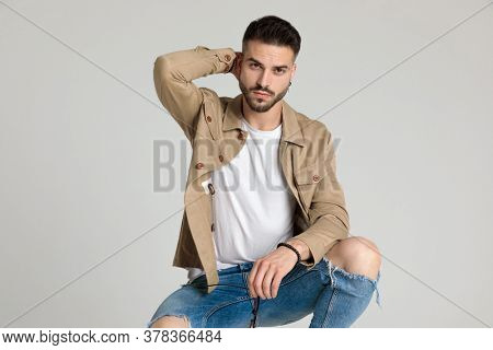 sexy young casual man in jacket holding hand behind neck, holding elbow on knee and posing, crouching on grey background