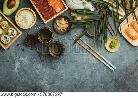 Overhead shot of ingredients for sushi, green tea and prepared maki and nigiri on dark blue background.