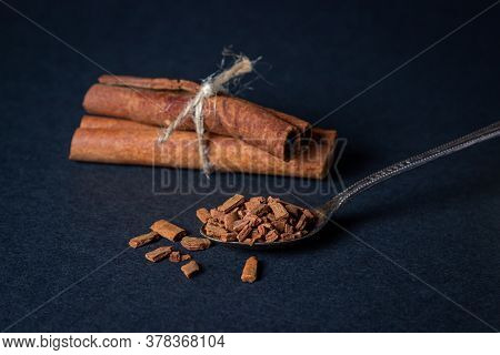 Cinnamon On A Black Background. Spoon With Crushed Cinnamon. Behind Two Sticks Of Cinnamon Tied With