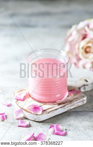 Ayurvedic Rose Moon Milk. A Trendy Relaxing Form Of Drink Before Bed. Milk With Rose Petals On A Lig