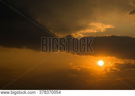 The Sun Receding Beyond The Horizon And Dark Clouds Above It
