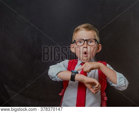 School Kid In School Uniform And Smart Watch. Pupil In Glassesand With Bag Looking At The Watch To K