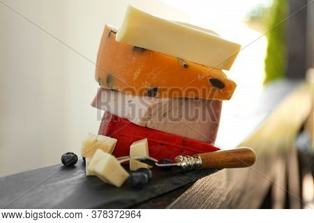 Different Types Of Delicious Cheeses And Fork On Wooden Railing Outdoors, Closeup