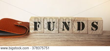 Wooden Cubes With Word Funds And Wallet On Table. Funding Business Concept.