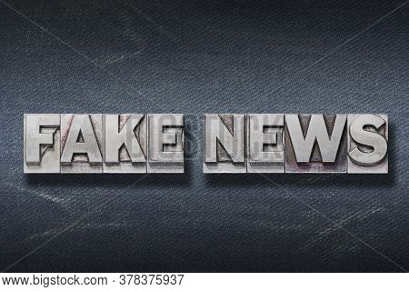 Fake News Phrase Made From Metallic Letterpress On Dark Jeans Background