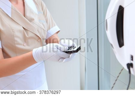 A Uniformed Maid Turns On A Window Cleaner Robot. Unrecognizable Photo. Photo In The Interior. The C