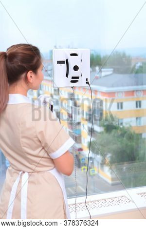 A Uniformed Maid Turns On A Window Cleaner Robot. Photos In The Interior. The Concept Of Cleaning An