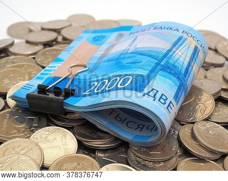 A Rolled Up Bundle Of Russian Banknotes Of Two Thousand Rubles Lies On A Pile Of Coins